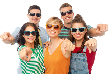 friendship, summer and people concept - group of happy smiling friends in sunglasses pointing at you over white background