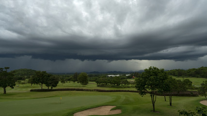 A play on a Hua Hin Thailand golf course is about to end as a sky is already black, a severe storm is approaching. Monsoon season typically brings heavy rains and high winds from Indian Ocean.