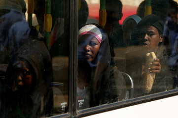 Migrants sit in the bus after disembarking from the humanitarian ship Aquarius at Boiler Wharf in Senglea, in Valletta's Grand Harbour