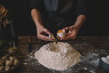 Food, cooking and baking concept. Making dough by female hands at bakery. Dough background. Preparation of the dough from fresh ingredients. On a rustic background. Ingredients for homemade baking.