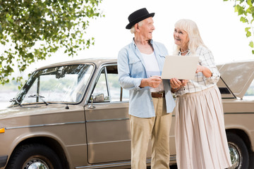Happy senior couple using laptop and looking at each other against beige retro car