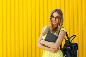 Pretty smiley girl student with book wearing funny toy round glasses and suitcase over yellow background