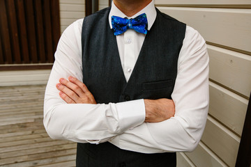 On the wedding day, the fashionable groom wears a blue bow tie with a dark blue vest.