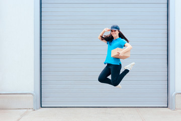 Female Delivery Worker Jumping in front of a Storage Warehouse