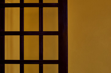 Wooden brown trellis. Wooden lattice on against a yellow plastered wall  background. Abstract background with copy space.