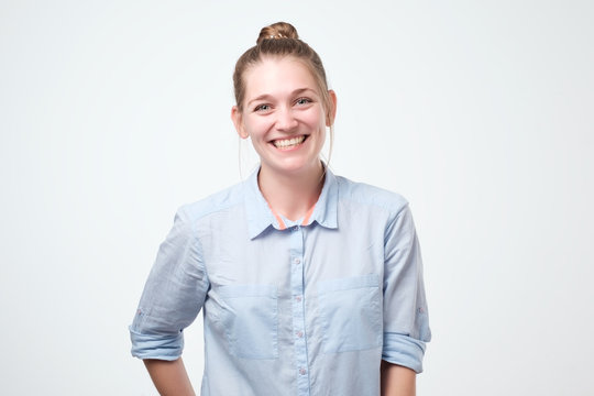 Happy cheerful young woman wearing her hair in bun rejoicing at positive news looking at camera