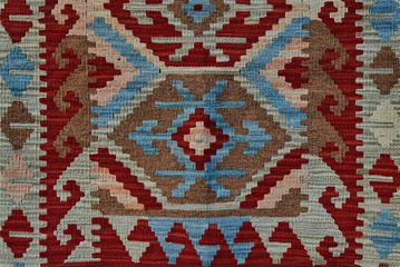 Close up of geometric patterned carpet. Hand woven rug with red, yellow, blue and other colors. Hand woven carpet with abstract design. Colorful carpet. Textile background. Abstract background.
