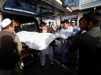 Afghan men carry a dead body of a victim inside an ambulance near the site of a suicide bomb blast in Kabul