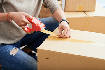 Crop guy using sticky tape to seal carton box while moving into new apartment