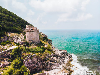 Beautiful scene, old building. Ancient defense tower on mountain in the Mediterranean sea. Paola tower is placed on Circeo promontory of Sabaudia, Italy. View from drone, aerial. Fotobehang