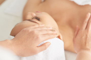 Close-up shot of hands of massage therapist touching head and shoulder of attractive woman during...