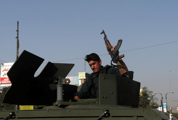 Afghan policemen arrive at the site of a suicide bomb blast in Kabul