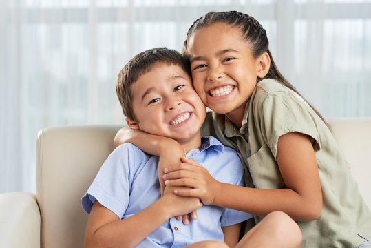 Cheerful Asian girl smiling and embracing cute boy while sitting on comfortable couch together