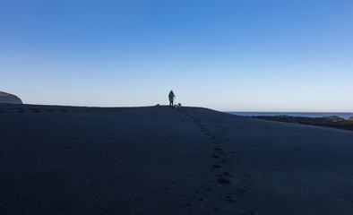 Lone hiker and two dogs silhouetted against blue sky