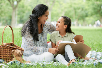 Adult Asian woman and sweet girl laughing and looking at each other while reading book during picnic in park