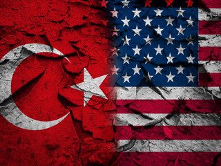 Sanction or conflict concept, USA flag against Turkey flag, on dry cracked earth background