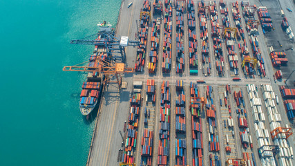 Container ship in export and import business and logistics. Shipping cargo to harbor by crane. Water transport International. Aerial view and top view.