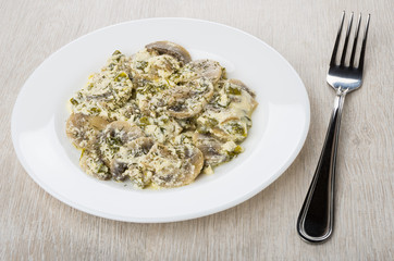 Cooked mushroom with sour cream in white plate and fork