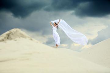 Fototapeta Piękna dziewczyna w białej sukni ślubnej z długim welonem na piaszczystej wydmie. obraz