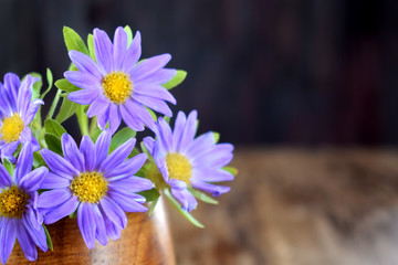Little violet asters in a wooden vase on a table