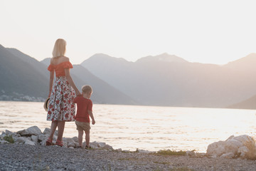 Back view of mother and son in red T-shirts looking at the sea at sunset in Montenegro