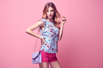 Wall Mural - Gorgeous long-haired Blonde woman wearing Stylish blouse and fashion Pink shorts. Beautiful sexy Lady in Trendy Summer Outfit, Makeup, Wavy Hairstyle. Sensual Female model in Studio