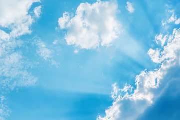 sunrays in blue sky with clouds