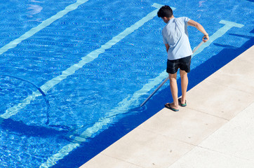 Guy in flip flops cleaning the swimming pool