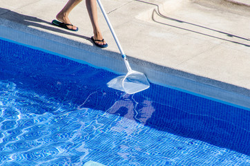 cleaning the pool side with a net