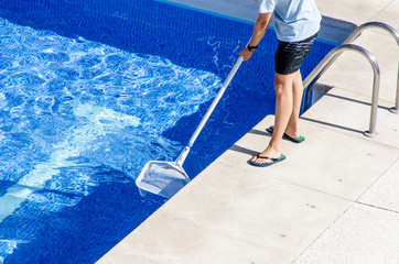 cleaning the swimming pool with a net