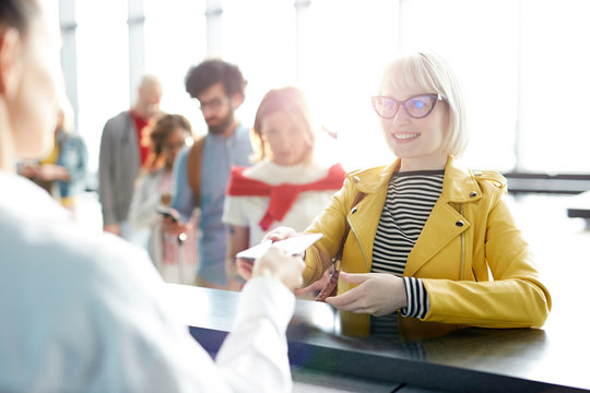 Young blonde woman giving documents while passing check in in airport in backlit