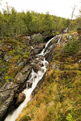 Beautiful view of the Voringsfossen waterfall. Bjoreio river . National park Hardangervidda, Eidfjord, Norway. Summer landscape in the mountains with a waterfall and fog. Foggy weather in the mountain
