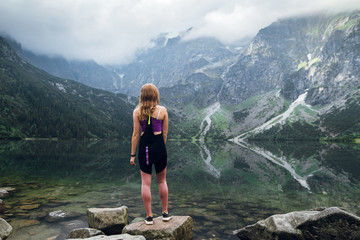 Rear view shot of young fit woman in sportswear looking on the scenic green hills and mountains in dark clouds on the Marine Eye lake, High Tatras, Zakopane, Poland. Foggy day
