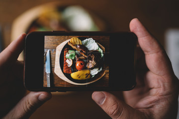 Food or technology concept. Man hands taking food photo by mobile phone. Close up of male hands holding modern smartphone, tasty dinner on the background. Toned image. Selective focus.