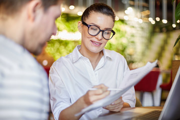 Casual woman in eyeglasses showing papers to coworking man sitting with laptop at table