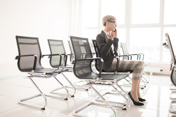 Modern woman in heel and elegant outfit sitting on chair in office hall and having phone call