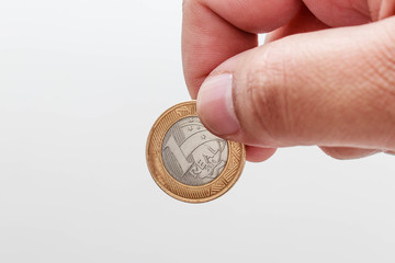 Male hand holding One Real, Brazilian coin white background
