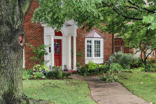 Entrance of nice brick house with bay windows after a storm that left branches and leaves littered over sidewalk and yard