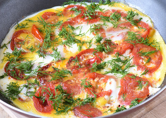 Rustic style. Scrambled eggs with tomatoes and dill in a frying pan