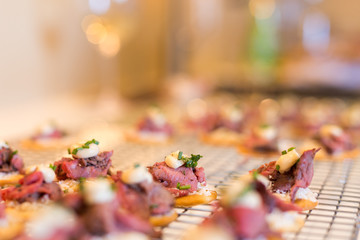 Close-up of steak canapes with chives on crackers.