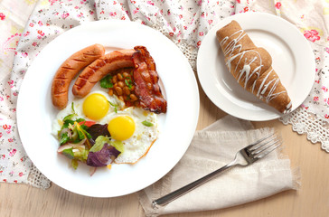 Breakfast with eggs, sausages and bacon. Light colors.