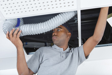 Man feeding ventilation hose above suspended ceiling