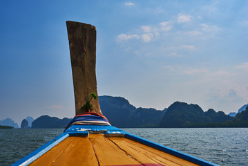 Ship nose front view long tail boat at sea Asia Thailand. View of the island, blue sky and sea  from  prow of a boat.  Traditional wooden boat  in Thailand. Travel and vacation concept.