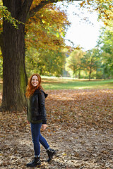 Young happy woman enjoying autumn day in park