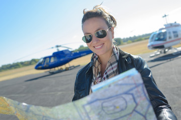 helicopter pilot looking at map on runway