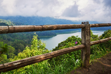 Wooden fence along  the shore of the lake. Low cloud shrouds the distant mountains. Tropical landscape with dramatic clouds in the sky. Lake and mountain view from a hill. Nature background.