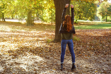 Ginger woman enjoying autumn day in park