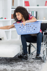Woman in wheelchair holding laundry basket and reaching to the side