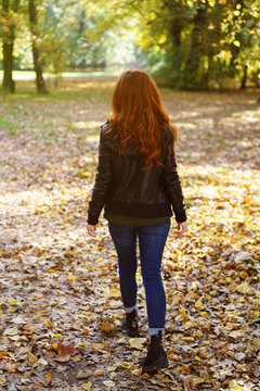 Red-haired woman walking in park on autumn day