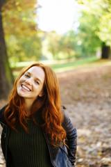 junge frau mit roten haaren steht lächeln im wald im herbst